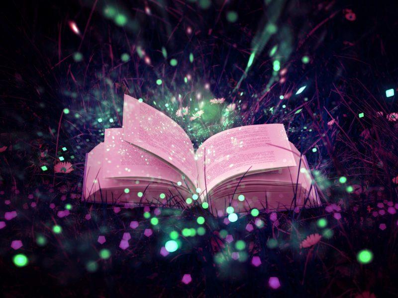 Открытая магическая книга лежит в траве