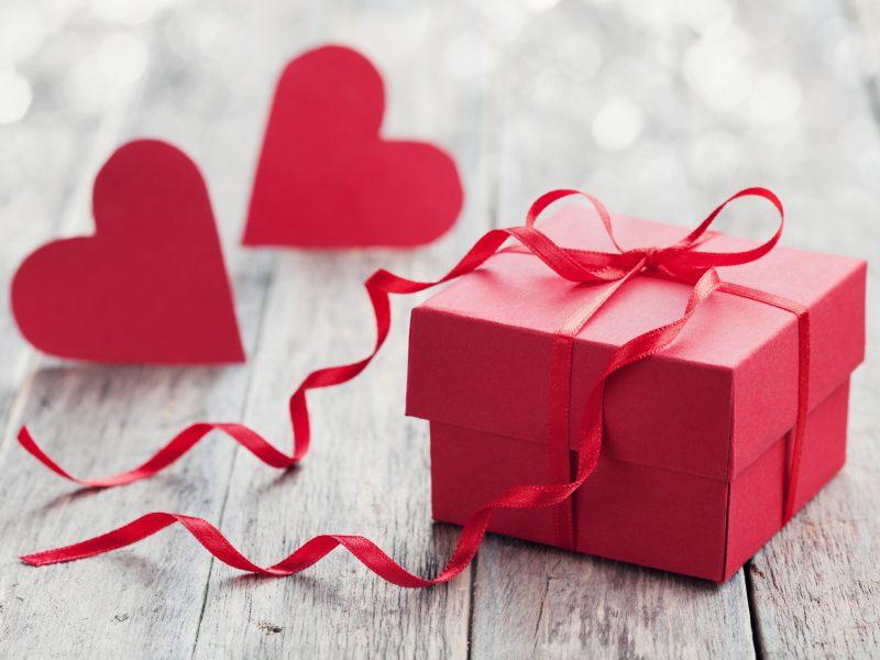 Красная коробка с подарком на столе с красными сердечками