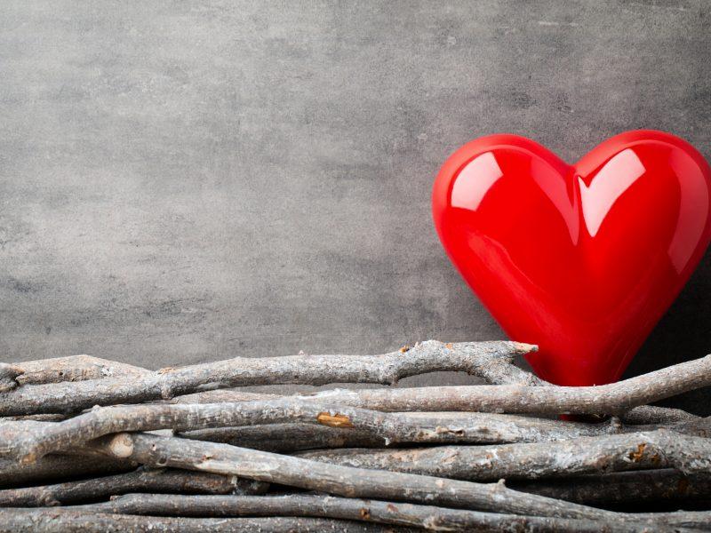 Большое красное сердце на сером фоне с деревянными прутьями