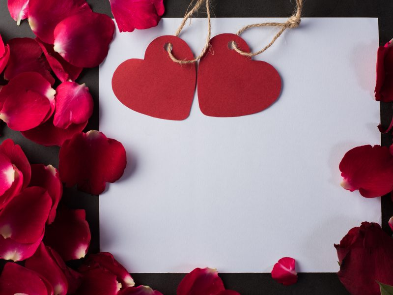 Белый лист бумаги с сердечками и лепестками роз