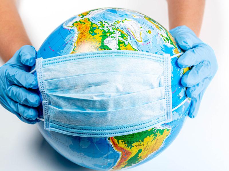 Руки одевают маску от коронавируса на глобус