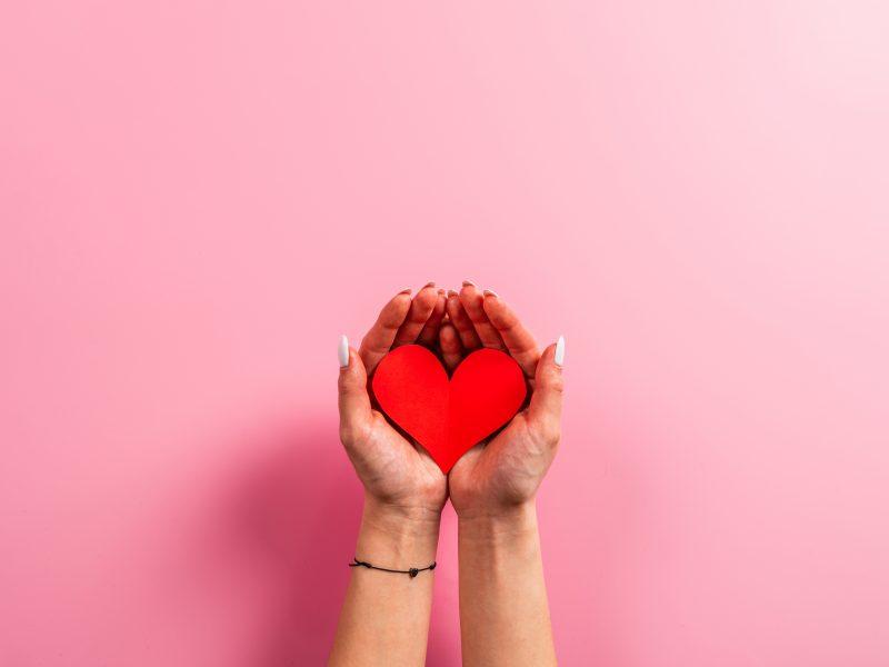 Красное бумажное сердце в руках на розовом фоне