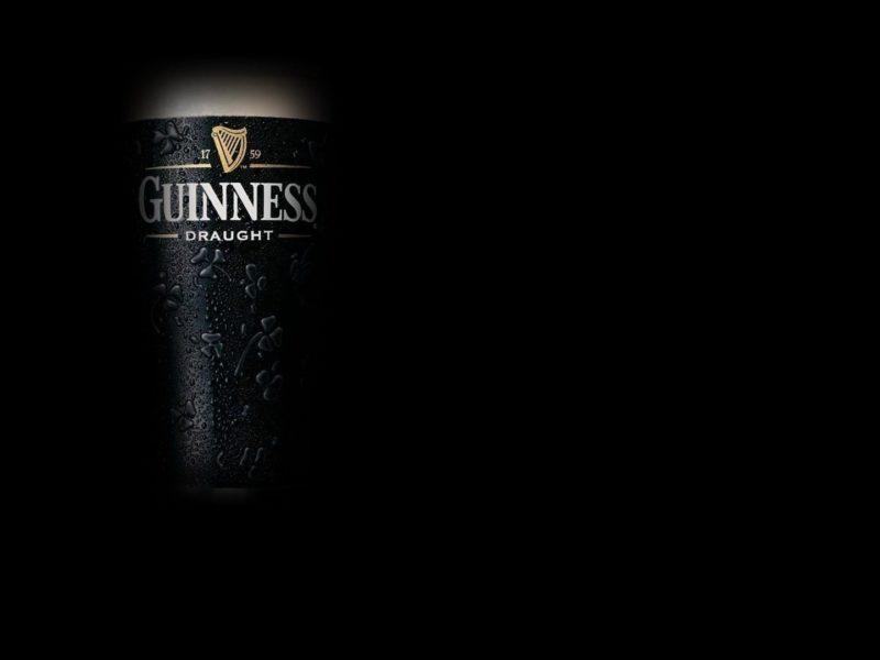 Темное пиво Guinness на темном фоне