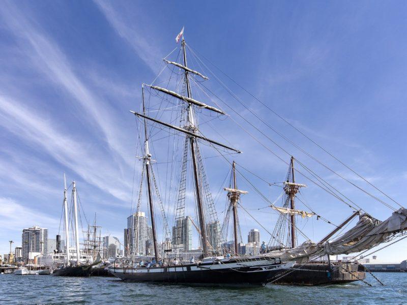 Большая парусная лодка на фоне голубого неба в порту у города