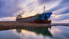 Старый ржавый корабль на берегу под красивым небом