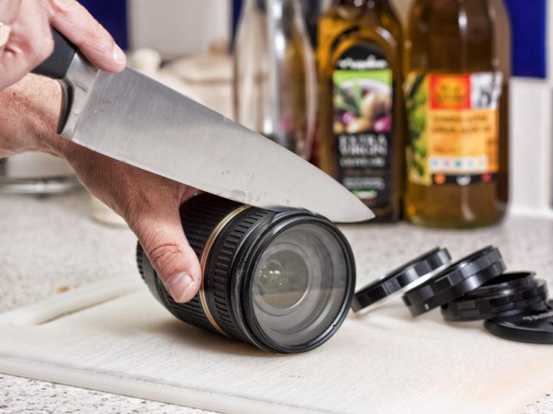 Мужчина нарезает ножом объектив фотоаппарата