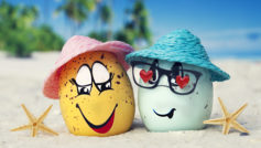 Два яйца в шляпах на песке с морскими звездами летом