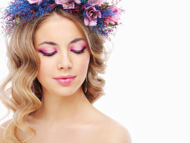 Девушка модель с закрытыми глазами с розовым макияжем на белом фоне