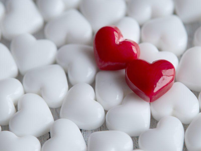 Два красных сердца лежат на белых