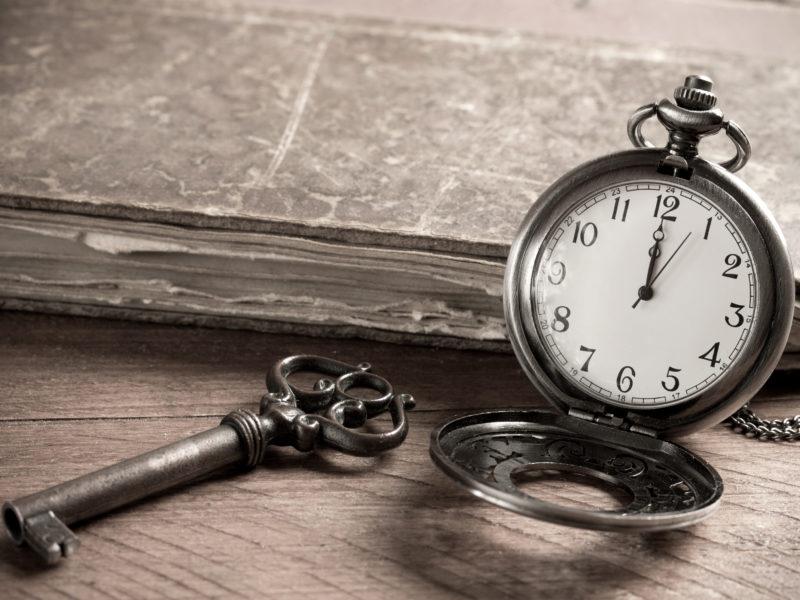 Карманные часы на столе с ключом и старой книгой