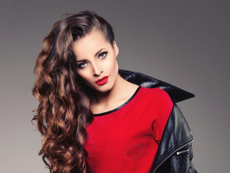 Красивая девушка в черной кожаной куртке и красном свитере