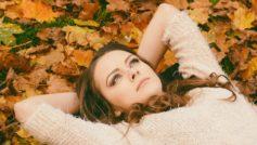 Мечтательная девушка в свитере лежит на земле
