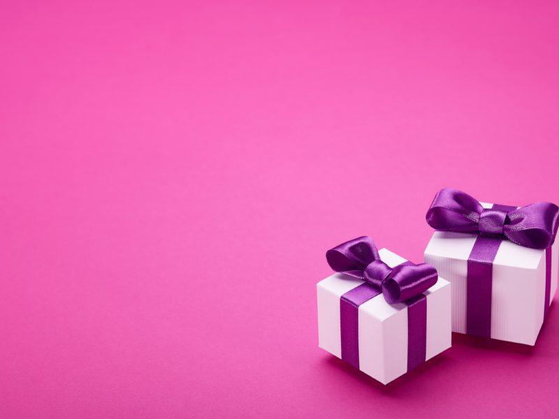 Два подарка с бантами на розовом фоне