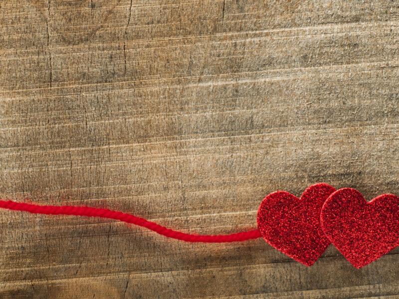 Два красных сердца со шнурком на деревянном фоне