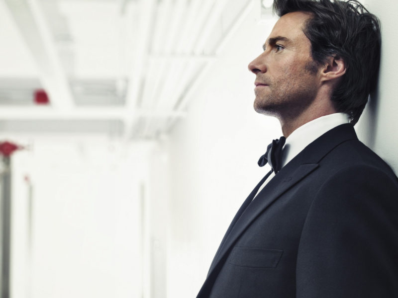 Мужчина в костюме, актер Хью Джекман у стены