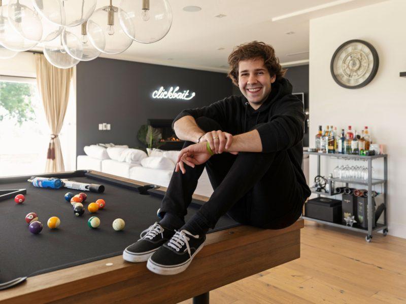Молодой блогер, юморист  Дэвид Добрик сидит на столе