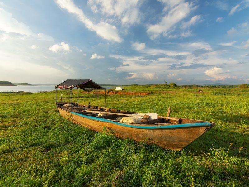 Большая деревянная лодка на зеленой траве