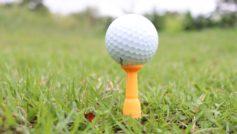 Мячик для гольфа на поле с зеленой травой