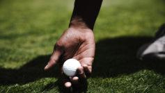 Белый мячик для гольфа в руке у мужчины на поле