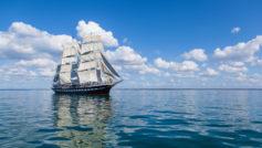 Большой парусный барк в небе над морем с белыми облаками