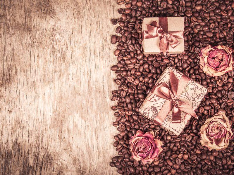 Подарки и розы лежат на кофейных зернах